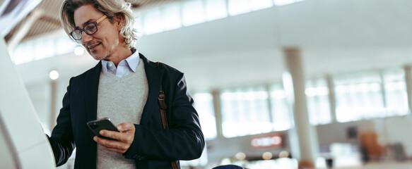 Fototapeta Businessman at airport making self check in obraz