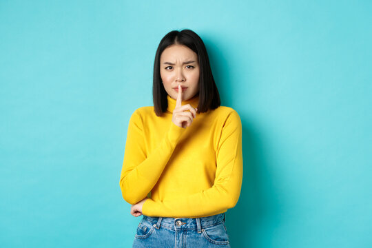 Disappointed asian woman telling to be quiet, scolding loud person with hush gesture, shushing at camera and frowning upset, standing over blue background