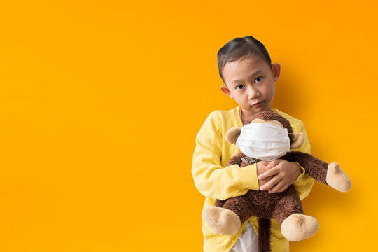 Asian child girl hugging doll wearing mask on yellow background