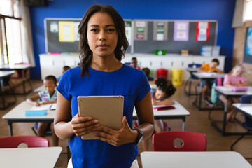Portrait of african american female teacher holding digital tablet in the class at school