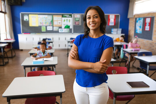 Portrait of african american female teacher with arms crossed smiling in the class at school