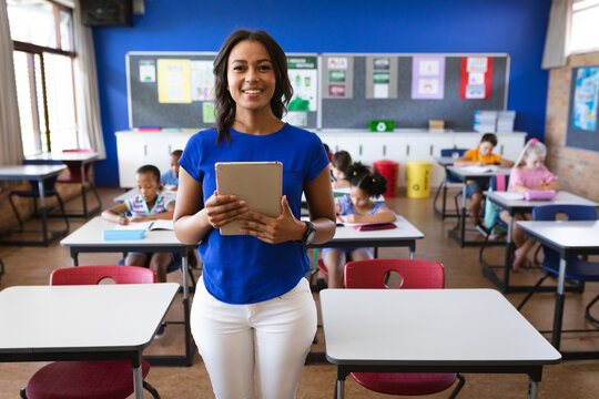 Portrait of african american female teacher holding digital tablet smiling in the class at school