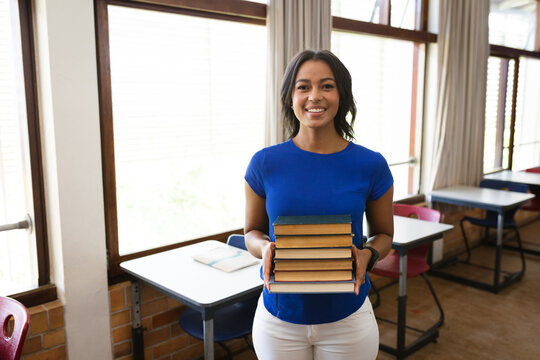 Portrait of african american female teacher holding a stack of books smiling in the class at school