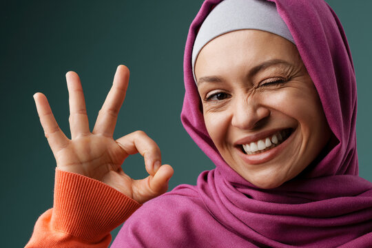 Middle eastern woman in hijab showing ok sign and winking