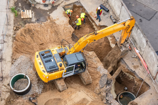 Excavator at a construction site while digging trenches for calcining sewer and drainpipes with a raised bucket, top aerial view.