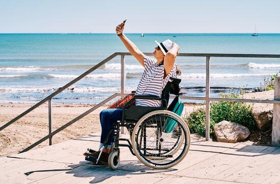 Woman in wheelchair taking selfie on beach