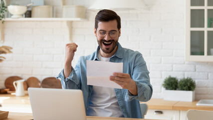 Young 35s overjoyed man sit at table hold paper sheet, read good news in letter, celebrate success...