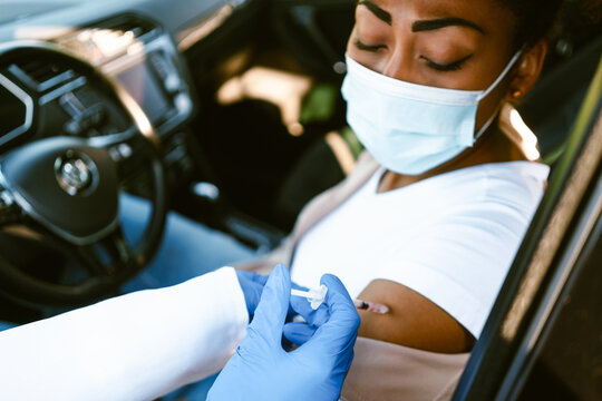 Health worker making vaccine injection to black woman in car