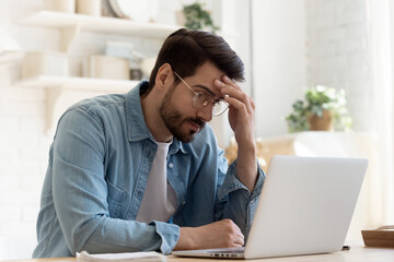 Fototapeta Bad news, lack of understanding of new app, info overload, device malware concept. Young man in glasses sit at table looks at laptop screen touch forehead feels confused has business or pc problems obraz
