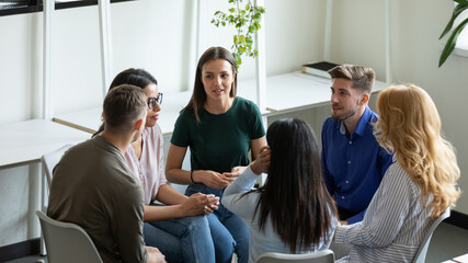 Obraz Diverse millennial team discussing mental health problems on group therapy meeting. Recovering addicts getting psychologist and community support, telling own addiction story on rehab session - fototapety do salonu