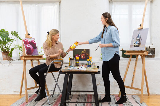 Content women painting together in art workshop
