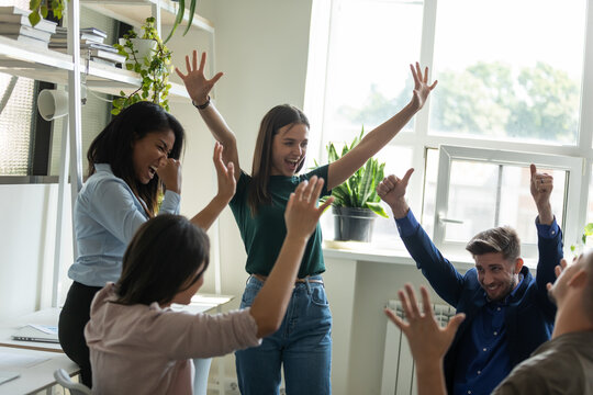Happy excited multiethnic team proud of good job result, meeting in office, celebrating business success, win, achieve, making winner gestures, laughing, shouting, having fun, enjoying party