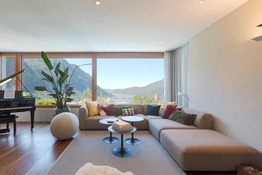 Front view of a living room with large, light-colored sofa and lots of pillows. Large window to the valley with lake view.