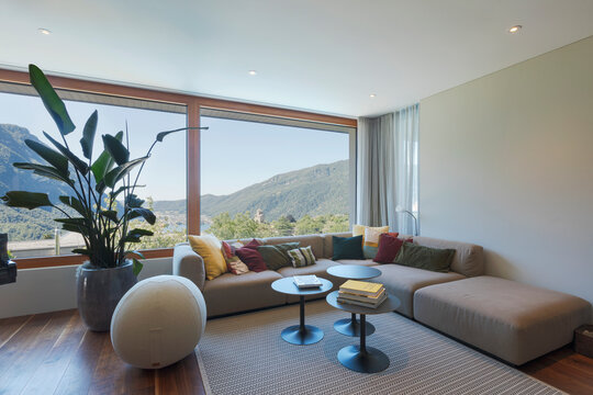 Living room with large, light-colored sofa and lots of pillows. Large window to the valley with lake view