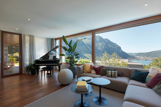 Living room with large light-colored sofa and lots of cushions and a black piano. Large window overlooking the valley