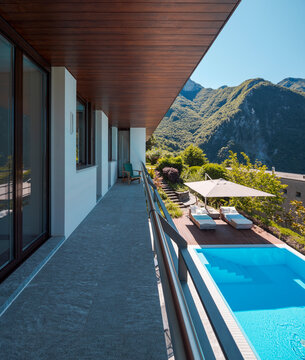 Balcony of villa with rock floor and wooden ceiling. Downstairs you can see the pool perfect for a swim