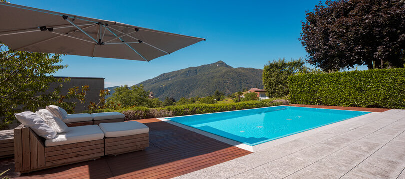 Large modern pool with two sun loungers for sunbathing and an open umbrella. View of the mountains of Switzerland
