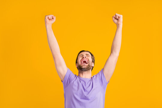 Photo of shocked funny young gentleman wear violet t-shirt smiling rising fists isolated yellow color background