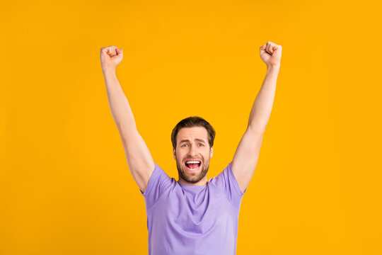 Photo of pretty lucky young guy dressed purple t-shirt yelling rising fists smiling isolated yellow color background