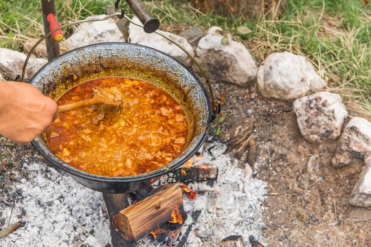 Metal cauldron boiling on a bonfire. Cooking on open fire, camping meal. Traditional preparation of goulash on a campfire