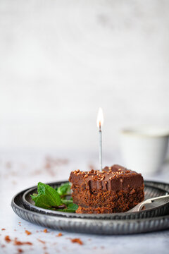 A Square of Chocolate cake topped with ganache, bronze sprinkles and a lit candle. A small piece has been remove from the square using the fork on the plate.