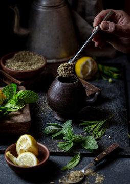Latin American hot drink yerba mate in clay cup, herbs amd lemon