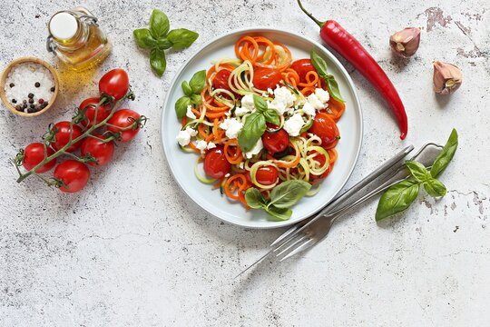 Warm salad from vegetable spaghetti, goat cheese and backed cherry tomatoes. Flat layot, copy space