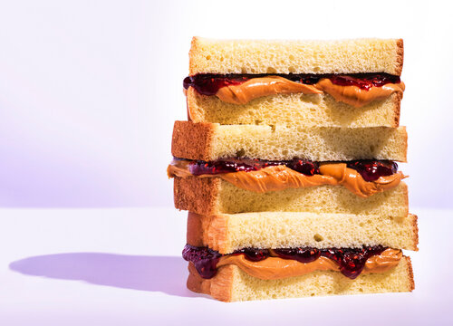 Stack of peanutbutter and jelly sandwiches with raspberry jam on a light purple background with dramatic lighting & shadows.