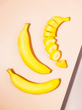 Overhead image of 2 whole and 1 sliced banana on geometric, pastel surfaces.