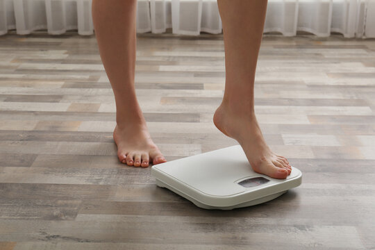 Woman stepping on floor scales indoors, closeup. Weight control