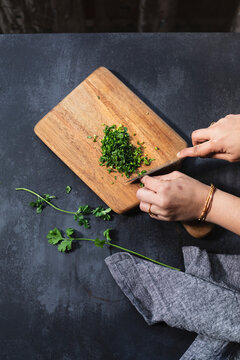 Coriander, Finely chopped on a chopping board in a slate kitchen setting. A hand chops the coriander