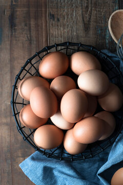Eggs in a wire basket with a whisk and wooden spoon.