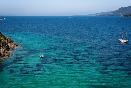 Top view of the turquoise water bay near corsican Porticcio town with boats in the water and mountains on the background. France 2021