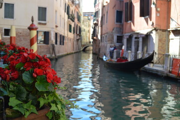 Fototapeta Venice, Italy. View of one of the numerous canals with venetian gondola and red flowers on the foreground. obraz