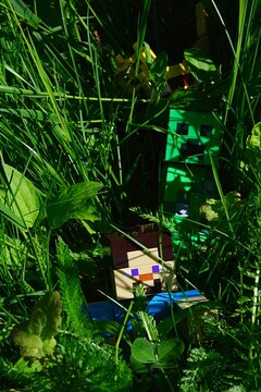 LEGO Minecraft large action figure of Steve chased by barely visible Creeper monster mob in long tall grass.