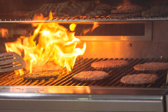 Flames Charbroil Hamburgers Cooking On A Grill