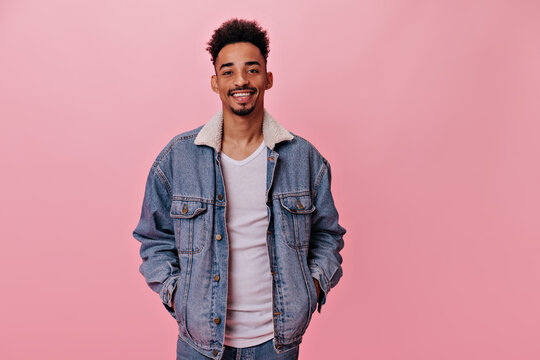Portrait of smiling man in denim jacket looks into camera. Handsome brunette guy in jeans and white tee widely smiles on pink background
