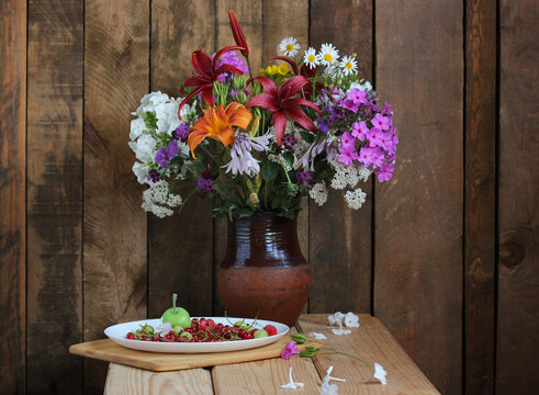bouquet of garden flowers in a clay jug and berries.