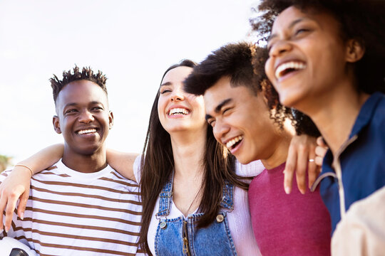 United multiethnic friends laughing and having fun together outdoors - Young adult group of funny people celebrating and hanging out - Summer holidays and college students concept - Focus on african