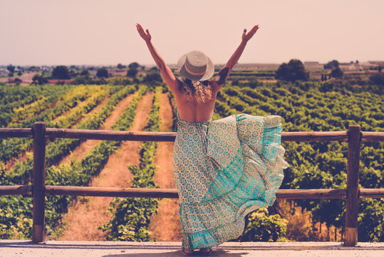 Trendy boho chic style back of woman opening arms for freedom feeling in front of a beautiful vineyard landscape - concept of outdoor and travel people lifestyle - fashion female dress back viewed