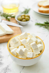 Bowl with pieces of feta cheese on light table