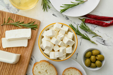 Bowl with pieces of feta cheese, green olives and fresh bread on light table