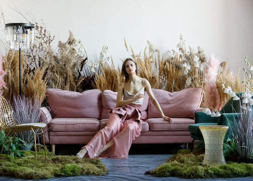Pleasant woman posing in a living room in the middle of tall grass