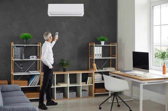 Businessman switching AC at work. Senior man standing in modern office interior turning on wall mounted air conditioner to enjoy warm air or cool breeze in summer heat. Comfort and lifestyle concept