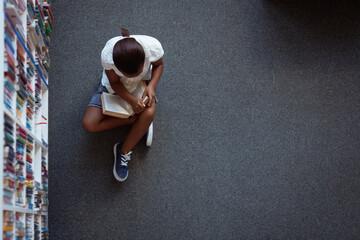 Overhead view of african american schoolgirl sitting on floor reading book in school library