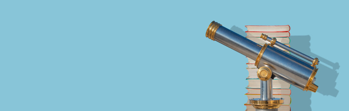 Banner with an old antique metal telescope standing near a stack of books at solid blue background with copy space and shadow, details, closeup. Concept exploration, education and travel.