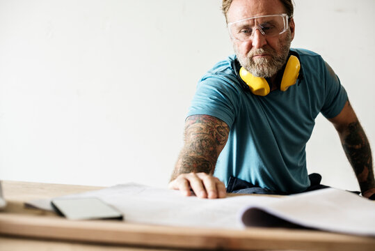 Man with tattoo looking to a blueprint