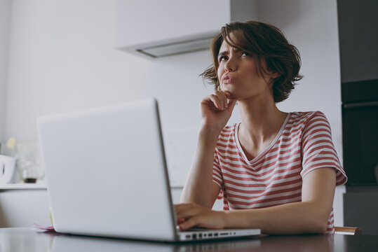Young puzzled pensive programmer freelancer housewife woman in casual clothes striped t-shirt use laptop pc computer work online prop up chin in light kitchen at home alone People lifestyle concept.