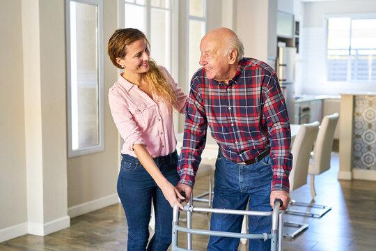 Junge Frau hilft Senior Vater beim gehen mit dem Rollator