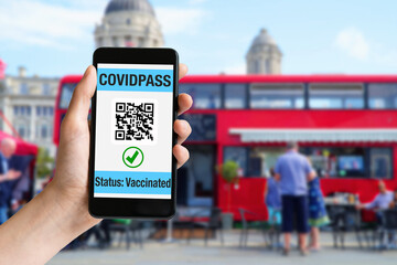 Hand holding mobile phone with covidpass on screen and red bus at London